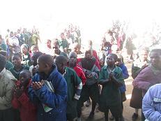 Joyful children singing after the school received building materials