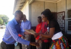 Caleb Chabauni(RN buildings Officer) being awarded by the District Commissioner